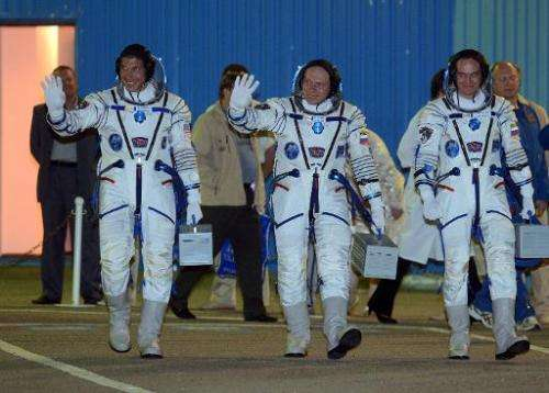 L-R: American astronaut Michael Hopkins and Russian cosmonauts Oleg Kotov and Sergei Ryazansky walk to their bus after at the Ba