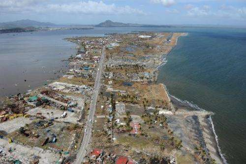 This aerial photo shows destroyed houses and the airport terminal (upper R) in the city of Tacloban, Leyte province, in the cent