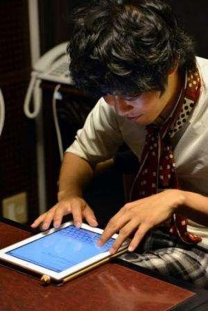 University student Akihiro Matsumura writes sentences on a tablet computer in Tokyo on June 19, 2013