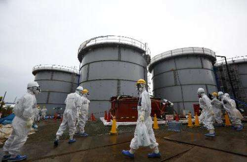 Members of the media and Tokyo Electric Power Co. employees wearing protective suits and masks walk past storage tanks for radio