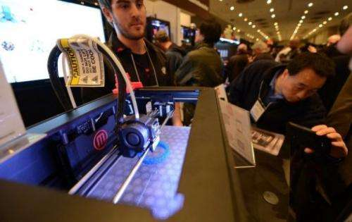 """Visitors look at a 3D printer at the """"Inside 3D Printing"""" event in New York on April 22, 2013"""