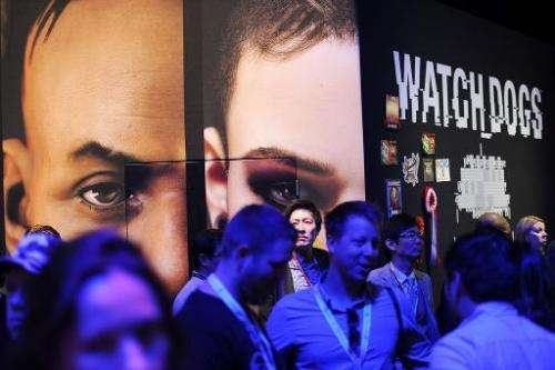 Visitors walk by the display for the game Watch Dogs by Ubisoft at the Electronic Entertainment Expo (E3) in Los Angeles, Califo