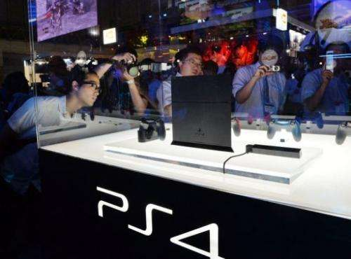 Visitors look at a display case containing a Sony PlayStation 4 at the Tokyo Game Show on September 19, 2013
