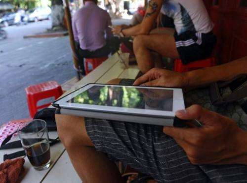"A customer uses his tablet to access the Internet at a ""wifi coffee shop"" in downtown Hanoi on August 1, 2013"