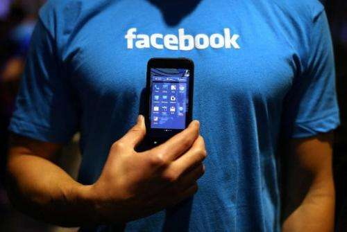 """A Facebook employee holds a phone that is running the new """"Home"""" program on April 4, 2013 in Menlo Park"""