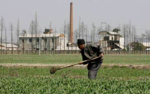 A farmer works next to a chemical factory in Yixing town, Jiangsu province, March 2006