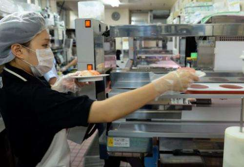 A kitchen worker places dishes onto the 'high-speed' food deliver lanes, in Tokyo, on June 10, 2013