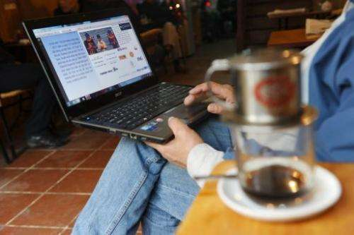 A man reads online news with his laptop at a coffee shop in downtown Hanoi on January 15, 2013
