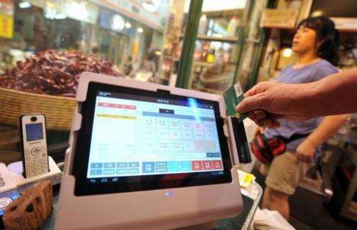 A manual cash register with a touchscreen tablet, seen at a sesame oil store in Seoul, on August 7, 2013