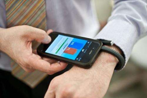 A man uses a Jawbone UP fitness wristband and its smartphone application in Washington on July 16, 2013