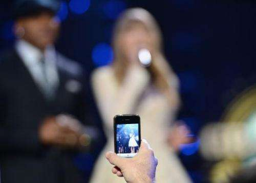 A music fan takes cell phone photo of LL Cool J and Taylor Swift onstage at Bridgestone Arena on December 5, 2012 in Nashville,