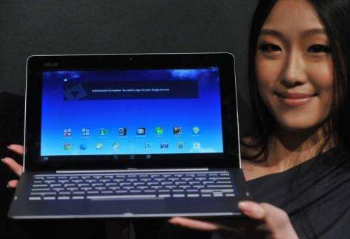 """An Asus employee displays the """"Transformer Book Trio"""" during a press conference in Taipei, on June 3, 2013"""