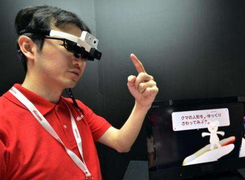 An engineer with Japan's telecom giant NTT Docomo wears a head mount display (HMD) to touch an animation bear for a demonstratio