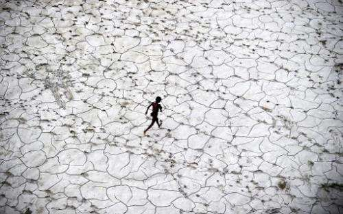 An Indian street child plays in a dry river bed after flood waters receded in Allahabad  on October 25, 2013