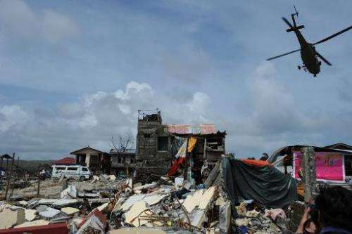 A rescue helicopter flies past a tattered national flag (C) and destroyed houses in the town of Hernani in Eastern Samar provinc