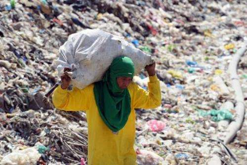 A scavenger carries recyclable materials at a temporary landfill in Payatas village, Quezon City, March 1, 2013