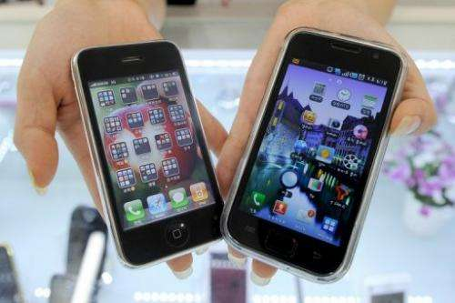 A shop manager shows Samsung Electronics' Galaxy S mobile phone (right) and Apple's iPhone 3G