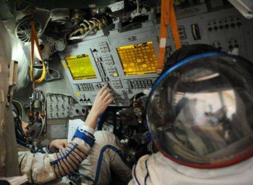 Astronauts sit inside a training module in Star City on May 6, 2009