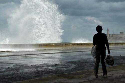 A woman observes waves hitting the Malecon waterfront in Havana, on December 13, 2010