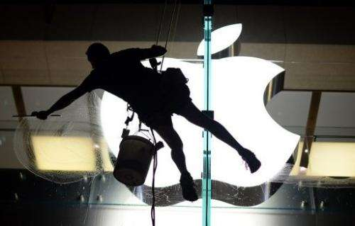 A worker cleans glass panels at the Apple store in the Central Business District of Sydney on Arpil 8, 2013