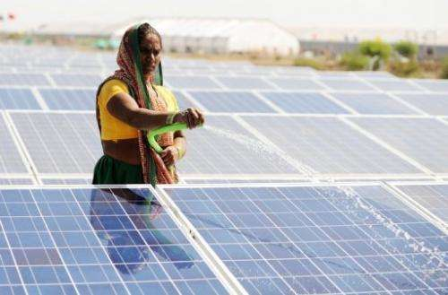A worker sprays water at India's first 1 megawatt canal-top solar power plant in Chandrasan village on April 22, 2012