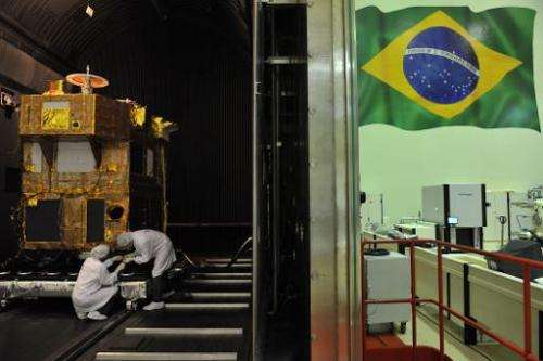 Brazilian researchers work inside a reinforced chamber on a CBERS satellite at the INPE headquarters, in Sao Jose dos Campos, so