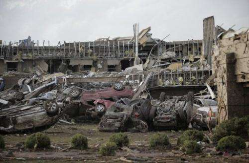 Flipped vehicles are piled up outside the heavily damaged Moore Medical Center on May 20, 2013