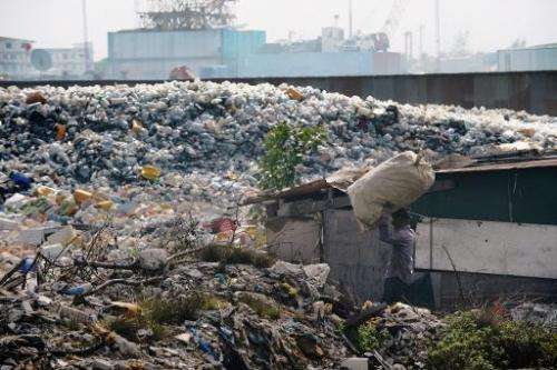 Fusin, a forty-year old Bangladeshi immigrant carries a sac of recyclable material as he walks in the country's largest trash du