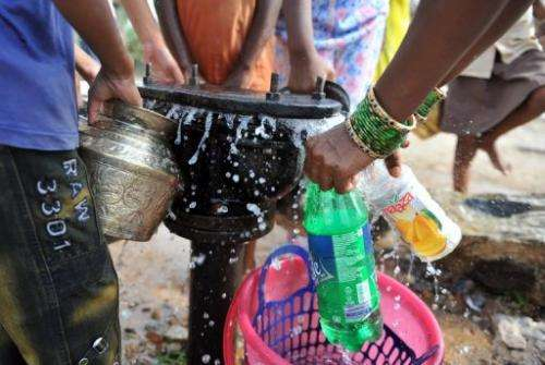Indian women fill containers with drinking water from a leaking pipe on the outskirts of Hyderabad on May 13, 2011