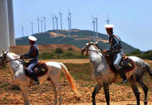 Moroccan guards ride past the Dahr Saadane wind farm in Tangiers on June 8, 2010