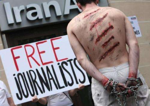 Reporters Without Borders activists protest in front of an Iran Air agency in Paris, on July 10, 2012