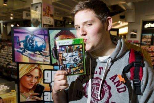 """Taylor Pelling poses with his copy of """"Grand Theft Auto V"""" at the HMV music store in central London, September 17, 201"""