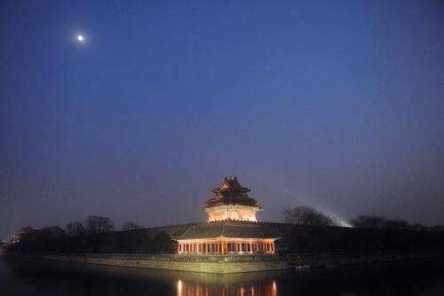 The moon shines over the Turret of Palace Museum at the Forbidden City in Beijing, December 13, 2013