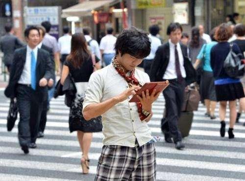 University student Akihiro Matsumura uses his tablet computer in Tokyo on June 19, 2013