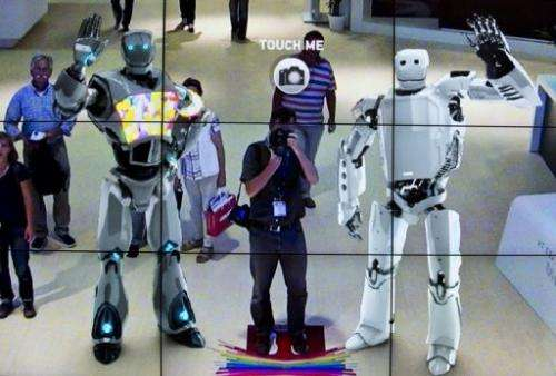 Virtual robots on a screen showing live footage of fairgoers during IFA in Berlin on September 3, 2012