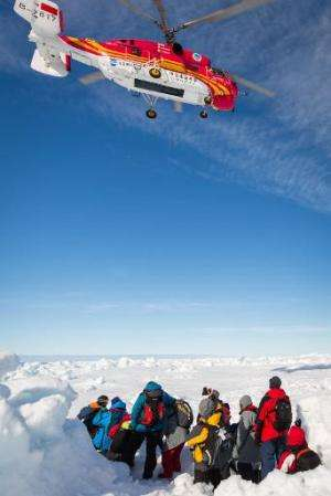 A helicopter from the Chinese icebreaker Xue Long hovers above passengers from the stranded Russian ship Akademik Shokalskiy in