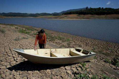 A local resident stands next to a boat near the bank of Jacarei river dam, in Piracaia, as a drought affects Sao Paulo state in