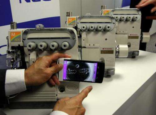 An NEC employee in Tokyo on November 10, 2014 demonstrates its new smartphone system for detecting fake products