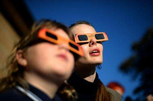 A woman (C) reacts while watching a partial solar eclipse with a child at the Sydney Observatory on May 10, 2013