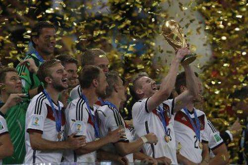 Germany's forward Andre Schuerrle (centre) holds the trophy as he celebrates with teammates after his team's victory in the fina
