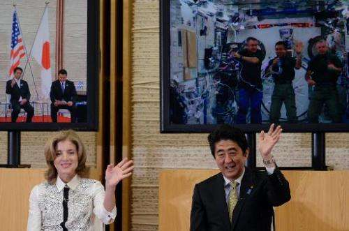 US Ambassador to Japan Caroline Kennedy (L) and Japanese Prime Minister Shinzo Abe wave fairwell to Japanese astronaut and ISS c