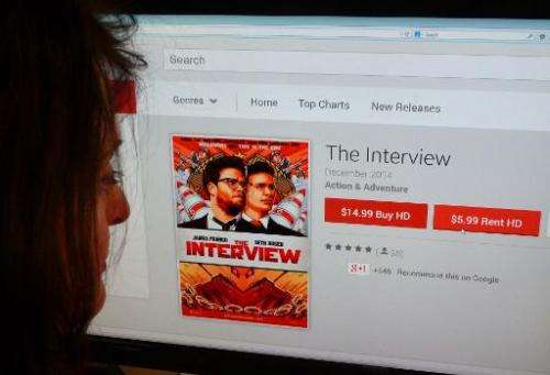 """A woman looks at the Google Play purchase page for """"The Interview"""" in Washington, DC on December 24, 2014"""