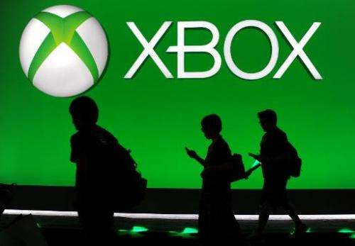 Attendees walk under the Microsoft Xbox One logo at the E3 Electronic Entertainment Expo, in Los Angeles, California on June 13,