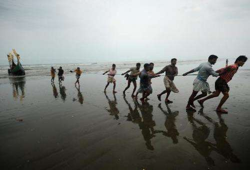 Bangladeshi fishermen, who are likely to be affected by climate change, pull a fishing boat from sea in Teknaf on June 16, 2012