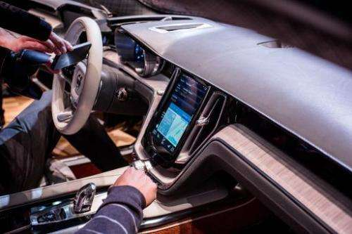 People look at Apple digital technology onboard the Estate Vovlo concept car at the Geneva Motor Show, on March 4, 2014