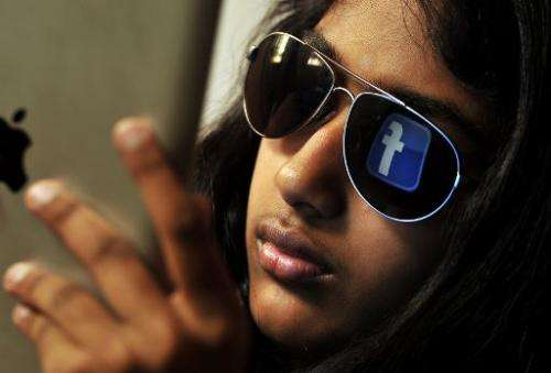 The 'Facebook' logo is reflected in a young woman's sunglasses as she browses on a tablet in Bangalore, India on May 15, 2012