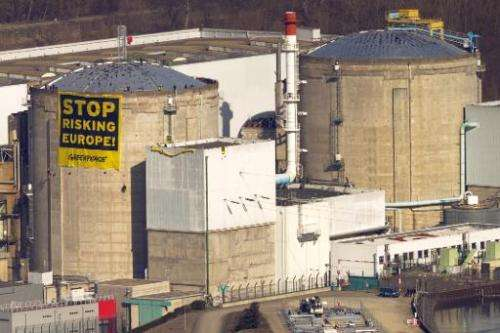 """Greenpeace activists display a banner reading """"Stop risking Europe"""" on a reactor of the nuclear power plant of Fessenh"""