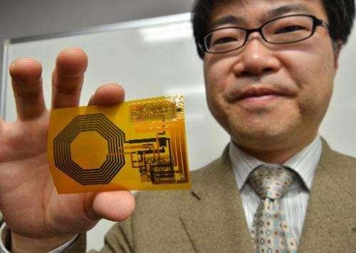 University of Tokyo professor Takao Someya holds the world's first disposable wireless organic sensor on February 9, 2014