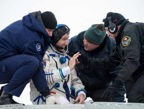 Photo taken on March 11, 2014, and released by NASA, shows US astronaut Michael Hopkins giving a thumbs up as he is helped from