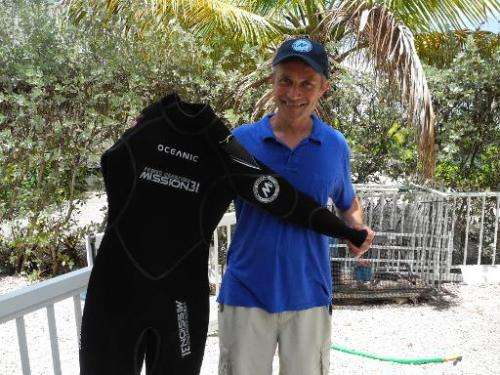 Fabien Cousteau, grandson of French oceanographer Jacques Cousteau, holds a scuba suit during an interview with AFP in Islamorad